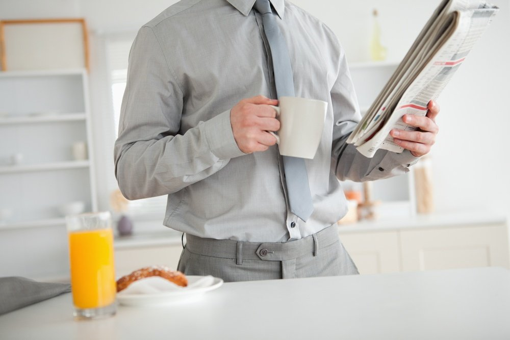 Businessman holding a newspaper while having breakfast in his kitchen.jpeg