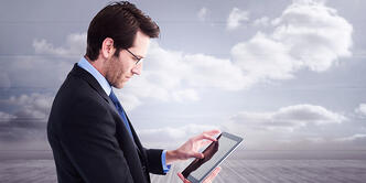 Businessman standing while using a tablet pc against clouds in a room