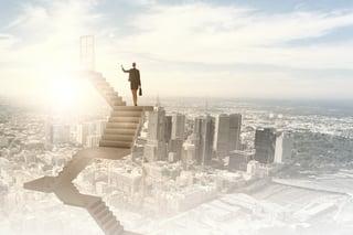 Businesswoman walking up staircase to door in sky.jpeg