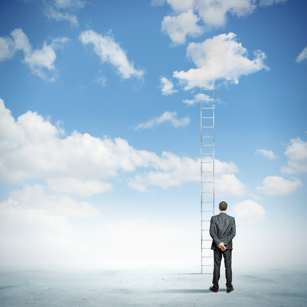 Rear view of businessman standing near ladder going high in sky.jpeg
