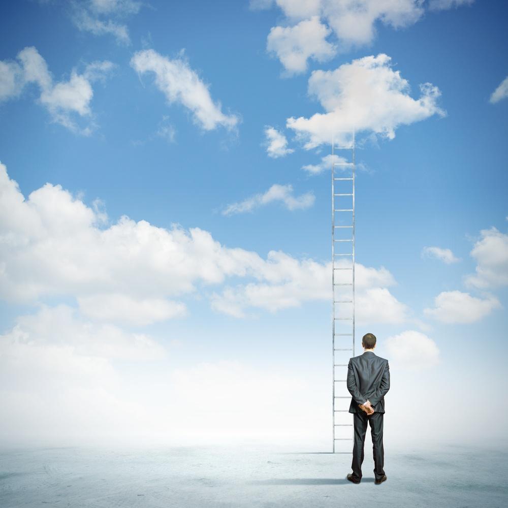 Rear view of businessman standing near ladder going high in sky.jpeg